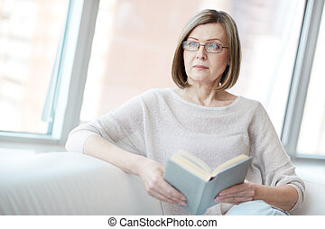Candid image of a mature beauty reading a book on her own time