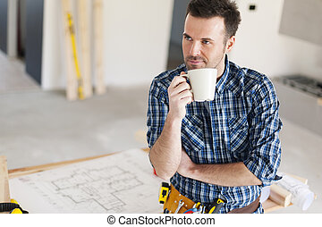 Candid construction worker relaxing with cup of coffee