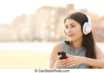 Candid girl thoughtful and listening to the music with a smart phone and looking away