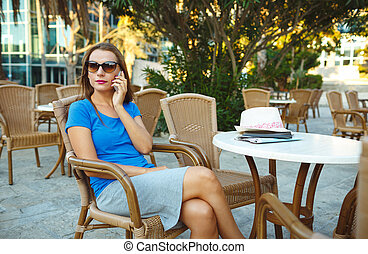 Candid image of a young woman talking on the phone in a cafe