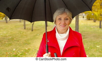 Candid Look - Waist up shot of senior lady walking in park...