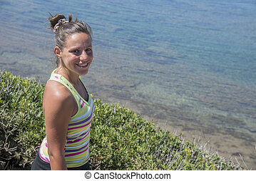 Candid portrait of attractive smiling brunette with no filters looking at camera with beautiful sea in the background.