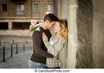 candid portrait of beautiful European couple with rose in love kissing on street alley celebrating Valentines day