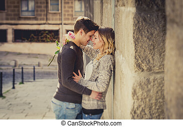 candid portrait of beautiful European couple with rose in...