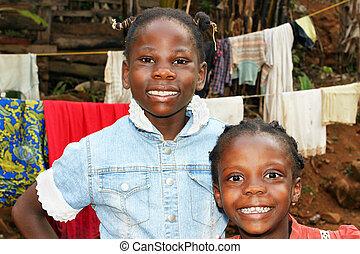 Real candid portraits of black African girls, sisters with big smiles, at home in front of clothesline in their backyard, great for future of developing countries.