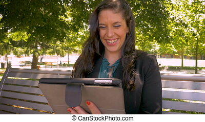 Candid real moment of a businesswoman laughing while on her tablet
