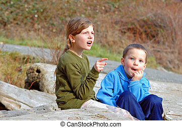 Candid shot of big sister and little brother outdoors catches unique expressions of real life.