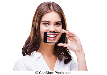 Candid smile. Beautiful young women holding mobile phone against her mouth and smiling while standing against grey background