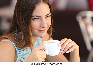 Candid woman thinking in a coffee shop holding a cup with an unfocused background