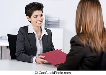 Candidate Giving File To Businesswoman At Desk