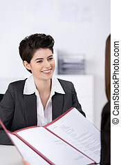 Candidate Looking At Businesswoman With Cv In Office