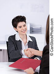 Happy young female candidate shaking hands with businesswoman at desk in office