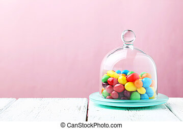 Candies in glass bell jar on white table