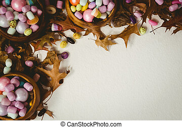 Candies with autumn leaves on white background