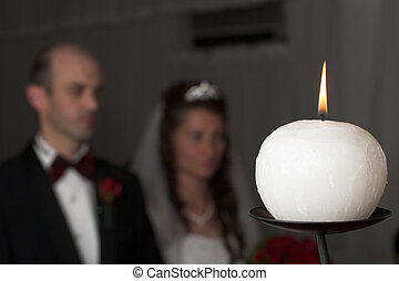 candle #6 - Single candle with bride and groom in background