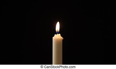 Candle - A single candle slowly flickers with a black ...