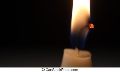 Candle - A single candle slowly flickers with a black...