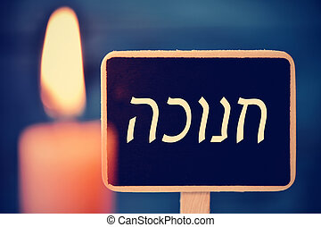 candle and chalkboard with the text Hanukkah in Hebrew