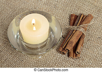 Candle and cinnamon sticks on burlap background