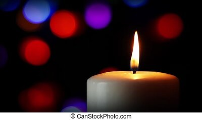 Loop with white pillar candle and flickering flame backed by colorful lights in the soft-focused background.
