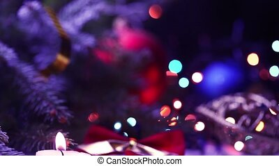 candle and decorations on a Christmas tree with blinking garlands