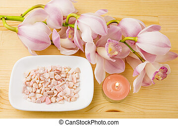 Candle and pebbles with orchid