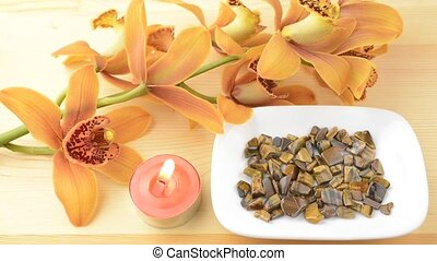 Candle and pebbles with orchid - Pink tin candle and tiger's...
