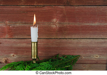 Candle at old barn wall and green decoration