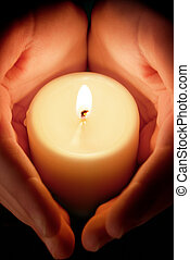 candle between the hands - hands protecting the glowing...