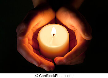hands protecting the glowing flame of a candle in the darkness
