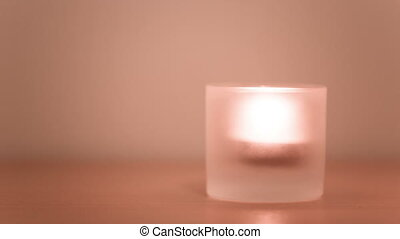 Candle burning in a glass candlestick close up video.
