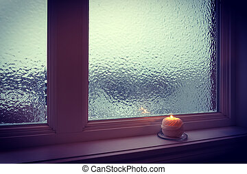 Candle burning near a frosted window in twilight