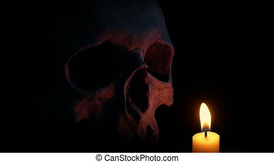 Candle Burning Next To Old Skull - Candles illuminating a...