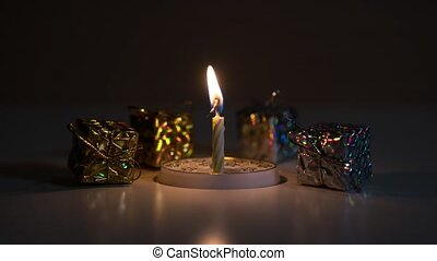 Candle burns in front of gift packages