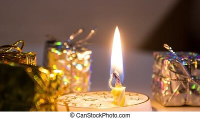 Candle burns in timelapse in front of the gifts