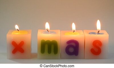 candle fire arranging X Mas word on white background and...