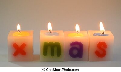 candle fire arranging X Mas word on white background