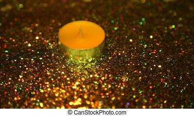 Candle fire in the dark against the background of color gloss
