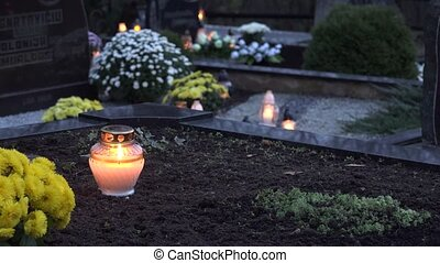 candle flame behind glass black ground graves in cemetery....