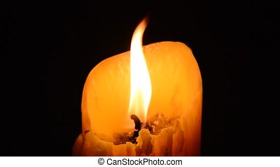 candle flame in the dark night and wind blowing light off