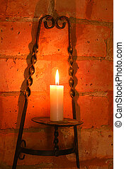 Candle in brass holder lighting wall of brick