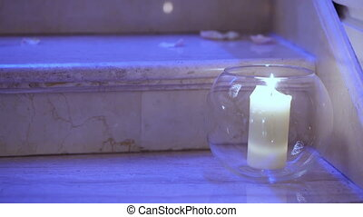 Candle in flask - Lonely burning candle on the marble steps....