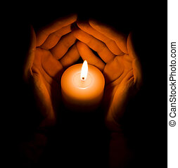 Candle in two hands at the dark