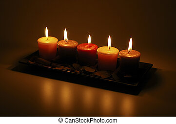 5 candles lit in a dark room.