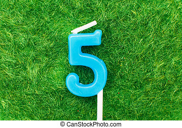 candle in the form of number 5 on the green grass background, a place for a greeting text