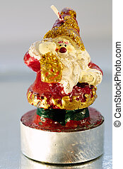 Candle in the shape of santa claus close up photo.