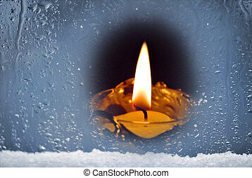 Candle in the snowy window.