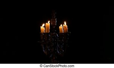 Two candles are extinguished in vintage candlestick on black background