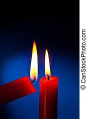 candle is lit - a red candle is lit with a match.