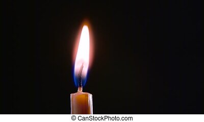 Candle is on and goes out. Black background. Close up -...